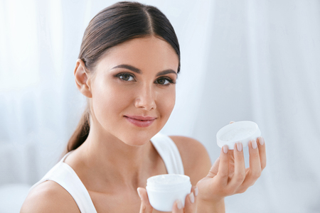 Skin Care. Beautiful Woman With Natural Face Beauty Holding Facial Cream In Bottle In White Interior. High Resolution 免版税图像
