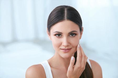 Natuurlijke schoonheid. Vrouw met mooi gezicht, zachte gezonde huid en natuurlijke gezichtsmake-up in wit interieur. Hoge resolutie