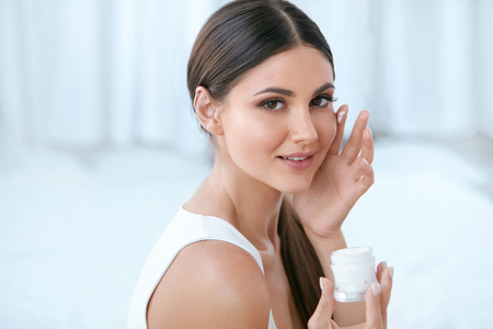 Woman Applying Facial Cream On Face Skin In White Interior Portrait. Beauty Girl With Lotion. High Resolution