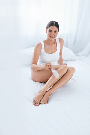 Body Care. Woman Touching Soft Smooth Leg Skin With White Feather In Light Interior. High Resolution