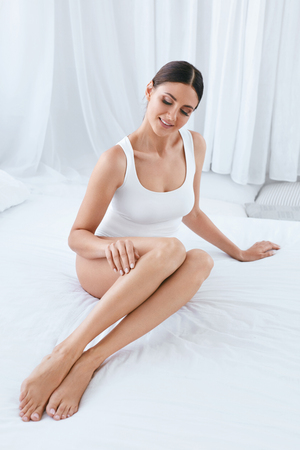 Body Skin Care. Beautiful Woman With Long Legs And Soft Smooth Skin In White Interior. High Resolution 免版税图像