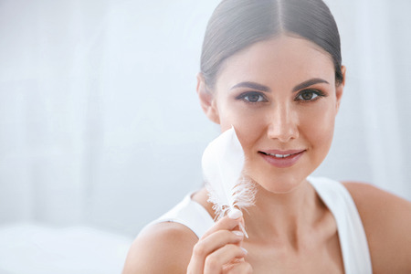 Beauty Skin Care. Beautiful Smiling Woman Touching Soft Smooth Face Skin With White Feather. High Resolution Stock fotó