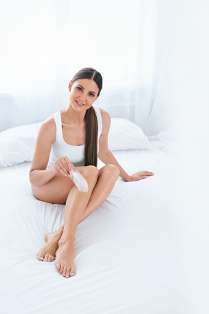 Skin Care. Woman With Soft Smooth Body Skin Touching Legs With White Feather In Light Interior. High Resolution