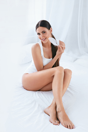 Beautiful Woman With Soft Body Skin And Smooth Long Legs With White Feather In Light Interior. High Resolution Banco de Imagens