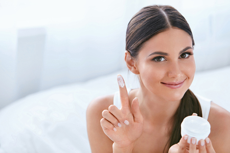 Beauty Face Skin Care Cream. Beautiful Smiling Girl With Cosmetic Facial Cream On Finger. High Resolution Фото со стока