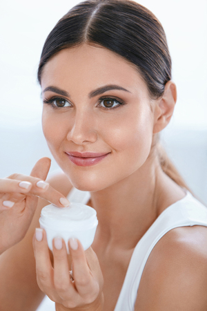 Face Skin Care. Beautiful Woman With Facial Cream In White Interior. Beauty Cosmetics. High Resolution