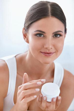 Soins de la peau du visage. Belle Femme Avec De La Crème Pour Le Visage Dans Un Intérieur Blanc. Cosmétiques de beauté. Haute résolution