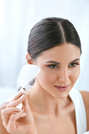 Beauty Skin Care. Beautiful Smiling Woman Touching Soft Smooth Face Skin With White Feather. High Resolution Reklamní fotografie