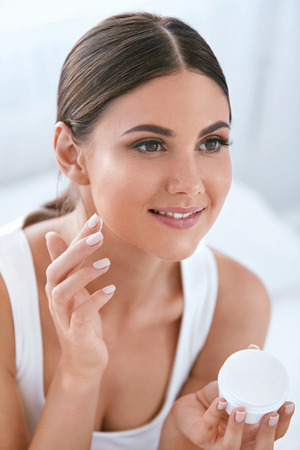 Beautiful Woman Applying Face Cream On Soft Healthy Facial Skin In White Interior.