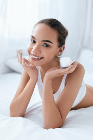 Skin Beauty. Beautiful Woman With Face Cream And Healthy Soft Facial Skin Lying On White Bed Portrait. High Resolution Stock Photo