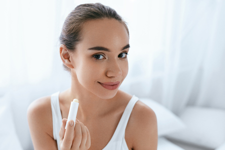 Lips Skin Care. Beautiful Woman Applying Lip Balm Portrait. Girl With Natural Makeup On Beauty Face. High Resolution