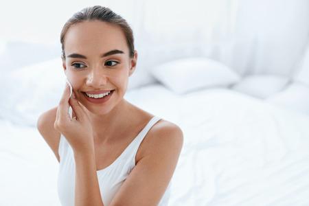 Bella donna che pulisce la pelle del viso con il tampone cosmetico bianco, rimuovendo il trucco.