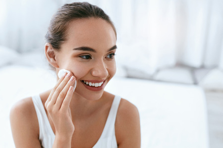 Beautiful Girl Cleaning Face Skin With White Cosmetic Pad.