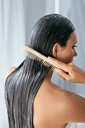Haarbehandlung. Frau mit Maske auf nassem Haar Nahaufnahme, Haare mit Holzbürste kämmen. Hohe Auflösung