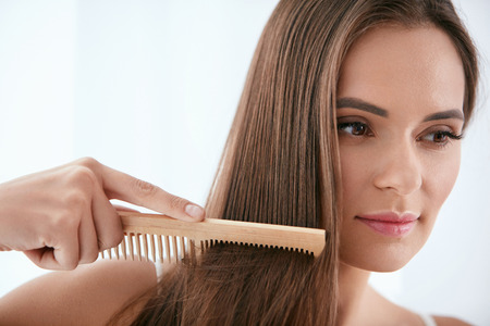 Hair Care. Woman Combing Beautiful Healthy Long Hair With Wooden Brush. High Resolution
