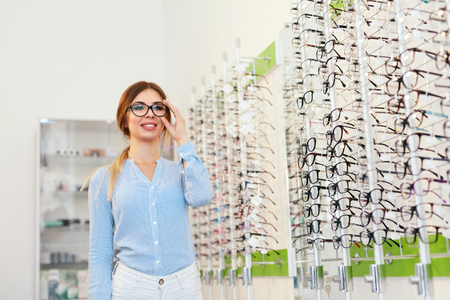 Eyeglasses Store. Woman Choosing Glasses For Eyesight Correction, Trying On Eyewear. High Resolution Standard-Bild - 115593702