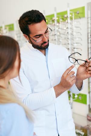 Optical Store. Eye Doctor Helping Woman Choosing Eyeglasses, Optician And Client. High Resolution Standard-Bild - 115593705