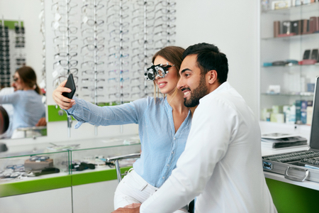 Eye Center. Woman Making Photo On Phone With Doctor On Eye Exam, Smiling Ophthalmologist With Patient. High Resolution Stock Photo