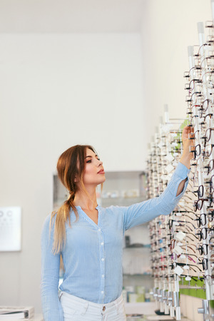 Optical Shop. Woman Near Showcase Looking For Eyeglasses, Choosing Eyewear. High Resolution Standard-Bild - 115593706