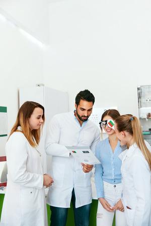 Eye Exam. Doctors Checking Woman Eyesight With Optometry Glasses, Ophthalmology Diagnostics. High Resolution Standard-Bild - 115593715