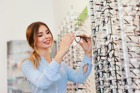 Optical Shop. Woman Near Showcase Looking For Eyeglasses, Choosing Eyewear. High Resolution Standard-Bild - 115593738