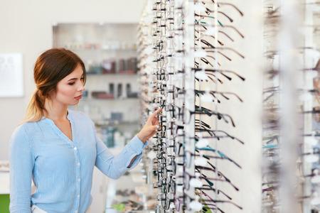 Optical Shop. Woman Near Showcase Looking For Eyeglasses, Choosing Eyewear. High Resolution Standard-Bild - 115593739