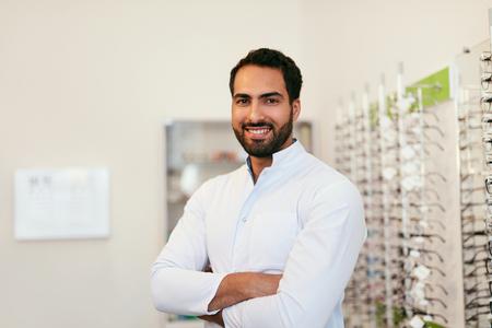 Optician Man Near Showcase With Eyeglasses At Glasses Shop, Smiling Male Optometrist. High Resolution Standard-Bild - 115593745