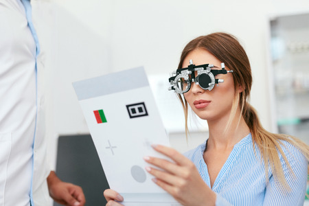 Eye Exam. Woman In Optometry Glasses Reading Eye Test Card, Eyesight Testing. High Resolution