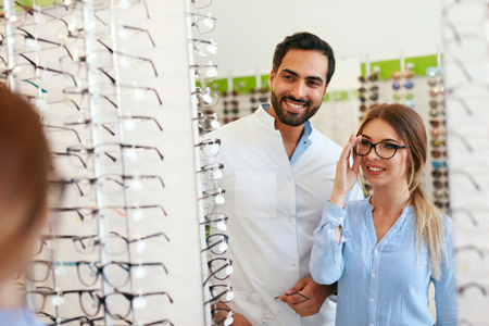 Eye Doctor With Woman Choosing Eyeglasses At Glasses Store, Female Trying On Glasses Near Mirror. High Resolution Banque d'images