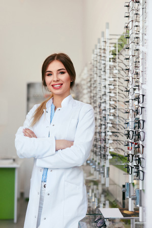 Optician Woman At Eyeglasses Store, Portrait Of Smiling Optometrist. High Resolution Stock Photo