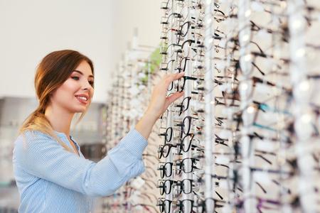 Tienda óptica. Mujer cerca de escaparate buscando anteojos, eligiendo gafas. Alta resolución