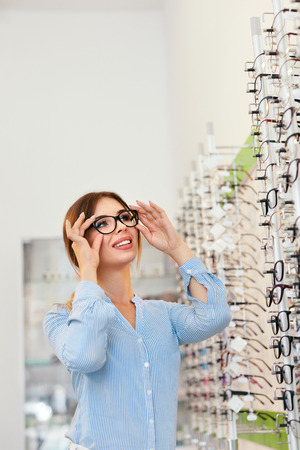 Eyeglasses Store. Woman Choosing Glasses For Eyesight Correction, Trying On Eyewear. High Resolution