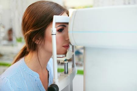 Sehprüfung. Frau, die Augensicht auf Optometriegeräte, Augenpflegezentrum überprüft. Hohe Auflösung