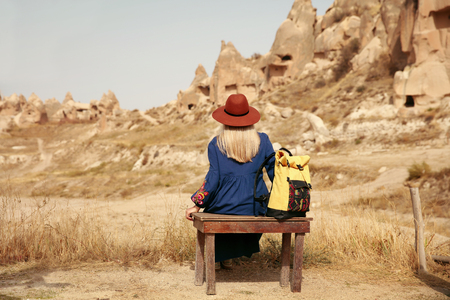 Travel. Woman Traveler In Hat With Backpack Traveling To Cave Town, Sitting On Bench Near Rocks. High Resolution