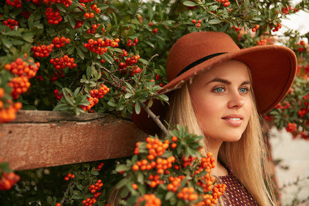 Portrait Of Beautiful Woman In Hat Near Tree With Berries, Stylish Girl In Branches. High Resolution 写真素材 - 112446671
