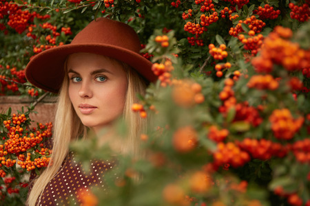 Portrait Of Beautiful Woman In Hat Near Tree With Berries, Stylish Girl In Branches. High Resolution