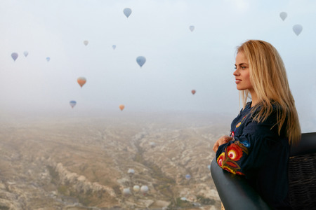 Traveling. Beautiful Woman Flying In Hot Air Balloon In Sky, Looking On Valley With Balloons. High Resolution