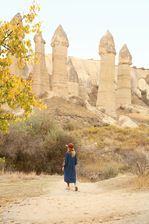 Travel. Beautiful Woman In Dress And Hat Traveling To Love Valley, Exploring Nature Of Cappadocia Turkey. High Resolution