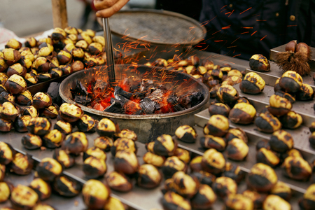 Street Food Market. Cooking Roast Chestnuts On Charcoal Closeup, Heap Of Cooked Chestnuts. High Resolution Banco de Imagens - 112888593