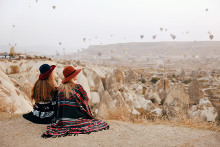 People Travel. Women In Hats Sitting On Hill Enjoying Flying Hot Air Balloons View At Cappadocia Turkey. High Resolution