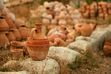 Clay Jug On Stone With Pottery Jars On Background, Heap Of Earthenware Pots. High Resolution