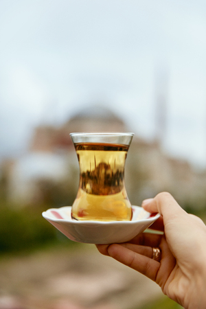 Turkish Tea Drink In Traditional Glass Cup In Hand With Mosque On Background. Eastern Drink. High Resolution 版權商用圖片