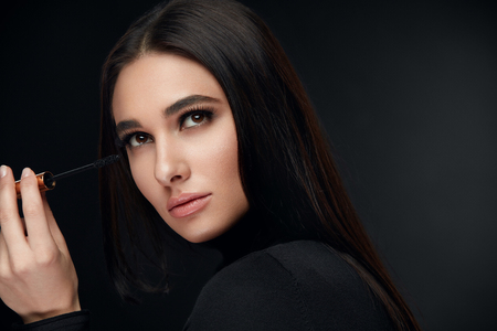 Beauty Makeup. Woman Face With Long Eyelashes Applying Black Mascara On Black Background. High Resolution