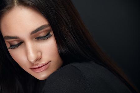 Wimpern Make-up. Frauen-Schönheits-Gesicht mit langen schwarzen Wimpern-Erweiterungen und schönem Make-up auf Schwarzem. Hohe Auflösung