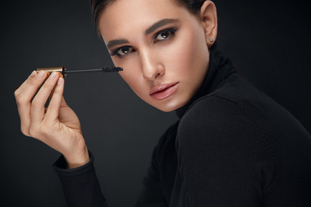 Makeup Cosmetics. Woman With Beauty Face Applying Black Mascara On Long Eyelashes. High Resolution