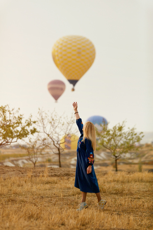 Beautiful Woman Trying To Reach Hot Air Balloon In Sky With Hand. High Resolution Standard-Bild - 115593748