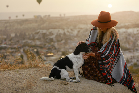 Woman In Hat Traveling With Dog. Girl Petting Animal On Hill In Sunset. High Resolution