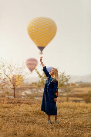 Beautiful Woman Trying To Reach Hot Air Balloon In Sky With Hand. High Resolution