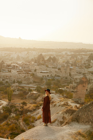 Travel. Woman In Dress Standing On Hill With Turkish Town On Background, Female Traveler At Cappadocia Turkey. High Resolution Stock Photo