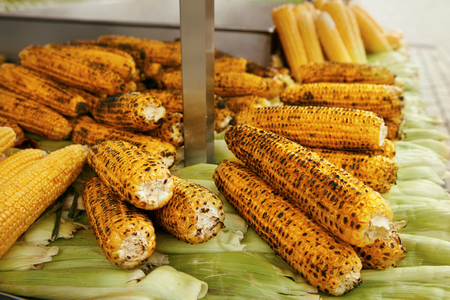 Roasted Corn At Eastern Street Food Market Closeup, Grilled And Raw Corn Cobs On Table. High Resolution